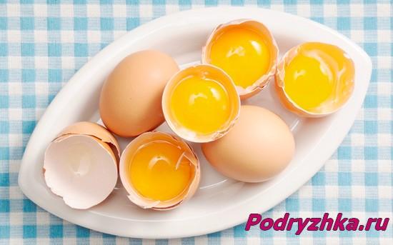 Разбитые пополам яйца на тарелке