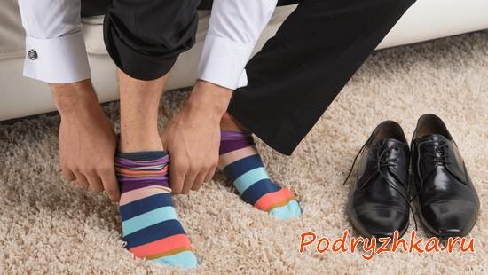 Мужчина одевает полосатые носки
