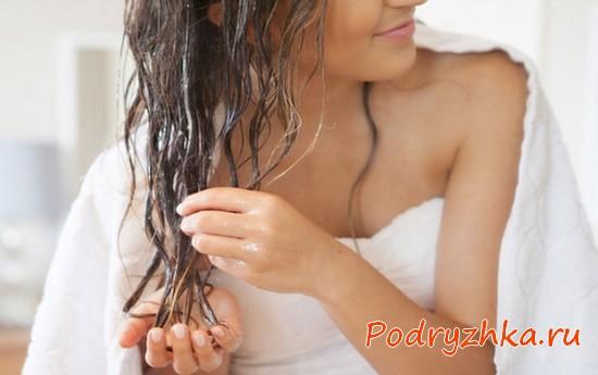 Девушка отжимает пряди после мытья головы