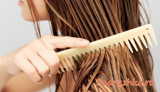 Девушка расчесывает мокрые волосы деревянной щеткой